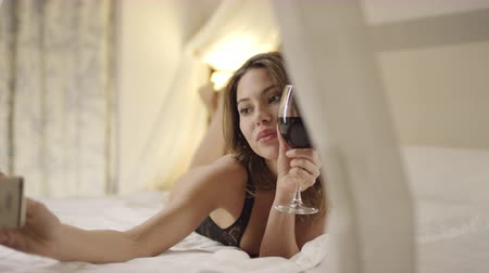 tek başına : Attractive woman drinks red wine and takes selfie on bed Stok Video