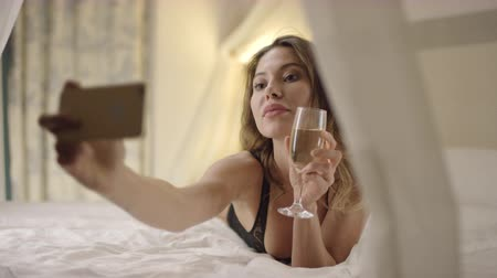 linen : Beautiful woman drinks white wine and takes selfshot on bed