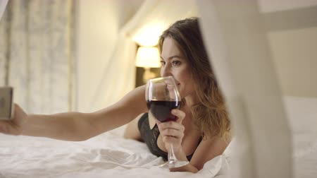 kırmızı şarap : Sexy woman drinks wine and takes selfie on bed