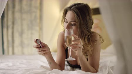 благодать : Woman in black lingerie drinks champagne and poses with credit card on bed