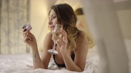 hazugság : Woman in black lingerie drinks champagne and poses with bank card on bed