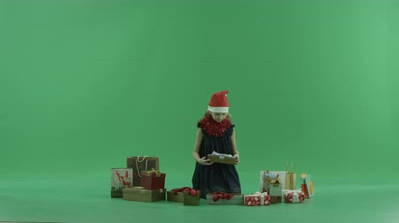 caixa de presente : Adorable little girl in Christmas hat opens empty Christmas present, chroma key on background