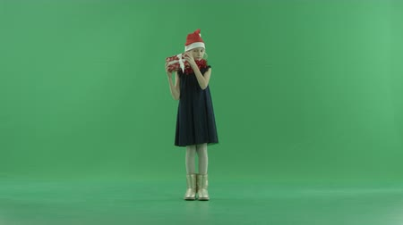 teljes test : Cute little girl in Christmas hat tries to understand what lies in Xmas present box, chroma key on background