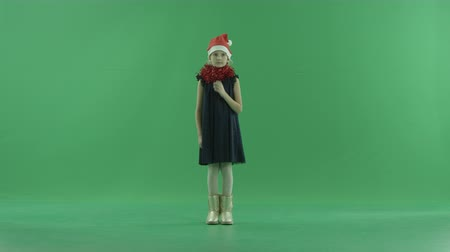 fulllength : Little pensive girl in Christmas hat, chroma key on background