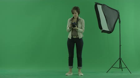 bluntly : A young woman checks camera on the green screen Stock Footage