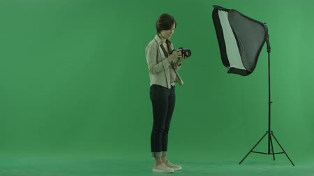 bluntly : A young woman is trying to use camera for the right hand side on the green screen Stock Footage