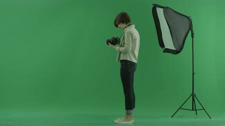 bluntly : A young woman is trying to use camera for the left hand side on the green screen
