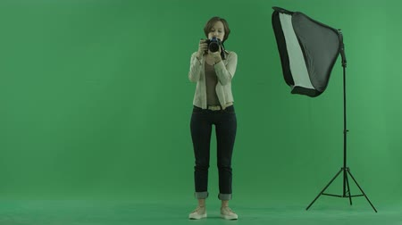 bluntly : A young woman is taking some photos of the viewer on the green screen