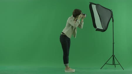 bluntly : A young woman taking photos on the right hand side on the green screen Stock Footage