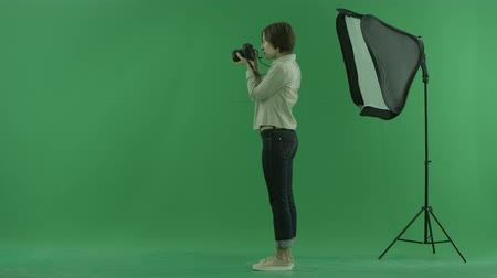 bluntly : A young woman taking photos on the left hand side on the green screen Stock Footage