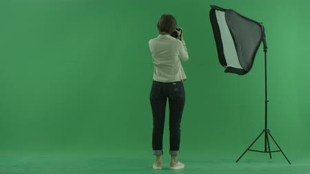 bluntly : A young woman taking photos on the side back to the viewer on the green screen