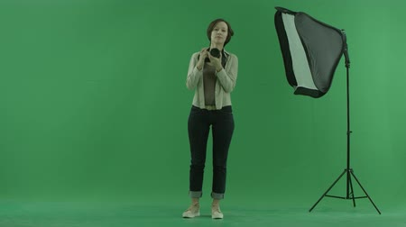 yayın : A young woman tries to take some photos of the viwer on the green screen Stok Video