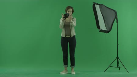 этап : A young woman taking photos of a viewer on the green screen and correct his standing