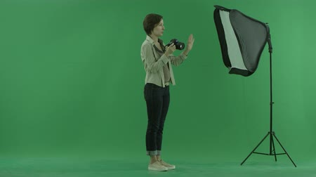 érték : A young woman taking photos on the right hand side on the green screen and corrects standing of a model
