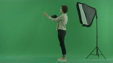 bluntly : A young woman taking photos on the left hand side on the green screen and corrects standing of a model