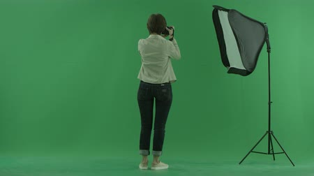 bluntly : A young woman taking photos on the side back to the viewer and make some corrections on the green screen