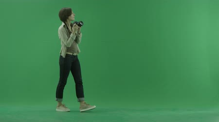 fotky : A young woman is going from the left side and taking photos around her on the green screen