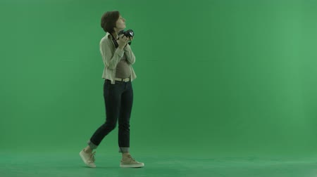photoshoot : A young woman is going from the left side and taking photos around her on the green screen