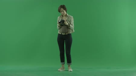 bluntly : A young woman is taking photos of herself on the front side on the green screen Stock Footage
