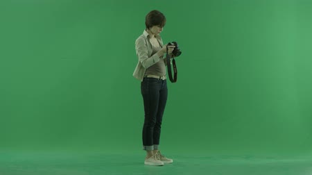 зеленый фон : A young woman is taking photos of herself on the right hand side on the green screen