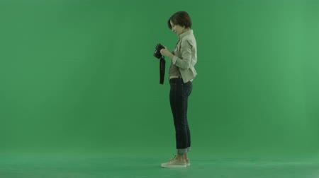 bluntly : A young woman is taking photos of herself on the left hand side on the green screen