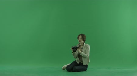fotky : Sitting young woman is taking photos around her on the green screen