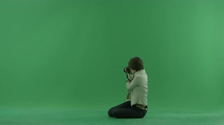 値 : Sitting young woman is taking photos on the left hand side on the green screen 動画素材