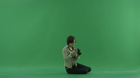 bluntly : Sitting young woman is taking photos on the right hand side on the green screen Stock Footage