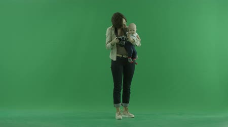 bluntly : A young woman with her child taking photos around herself on the green screen