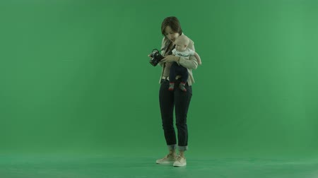 bluntly : A young woman with her child taking photos on the left hand side on the green screen
