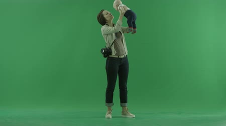 bluntly : A young woman lift her child on the green screen