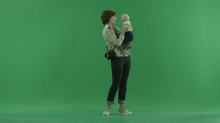 bluntly : A young woman is talking with her baby on the green screen Stock Footage