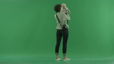 bluntly : A young woman lifts her baby on the side back to the viewer on the green screen Stock Footage