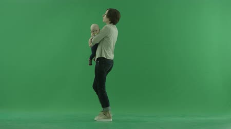 esquerda : A young woman going from the left side with her baby on the green screen