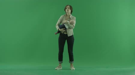 bluntly : A young woman rocks her baby on the green screen Stock Footage