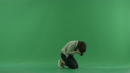 bluntly : Sitting young woman is taking macro photos on the right hand side on the green screen