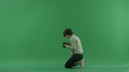 тестирование : Sitting young woman is taking macro photos on the left hand side on the green screen