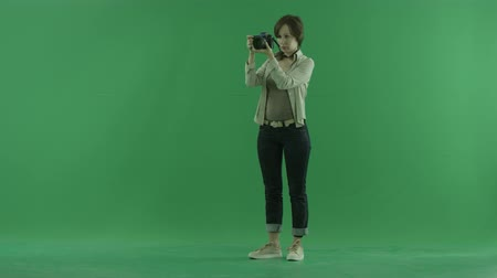 ladění : A young woman is tuning her camera on the green screen