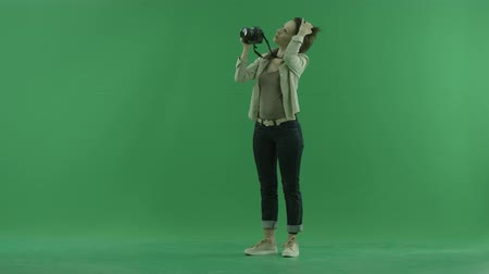 ladění : A young woman is taking photos upper herself on the left hand side on the green screen