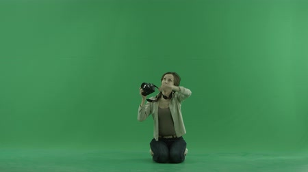 fotky : Sitting young woman is taking photos upper her on the green screen