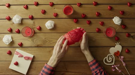 olhando para baixo : Young man looks at plastic human heart by wooden table, top view Vídeos