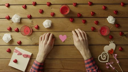 minimalizm : Young man with handmade hearts of paper sits by table, top view