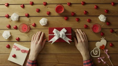 table top shot : Adult man gets holiday present in gift box on wooden table, top view