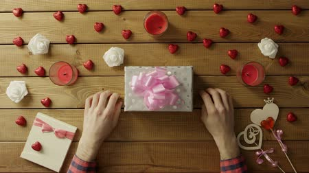 envolto : Young man puts valentine onto present box, top view Vídeos