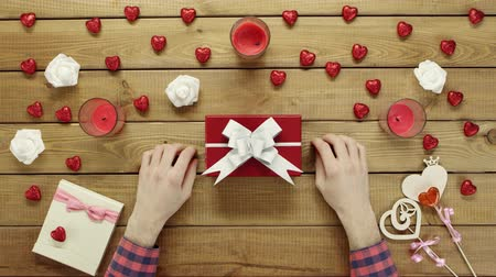 table top shot : Man puts valentine onto present box for his wife, top view Stock Footage