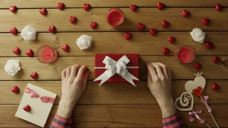 loved : Man puts valentine onto present box for his loved one, top view