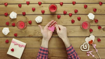 table top shot : Joyful man with paper heart sits by wooden table, top view Stock Footage
