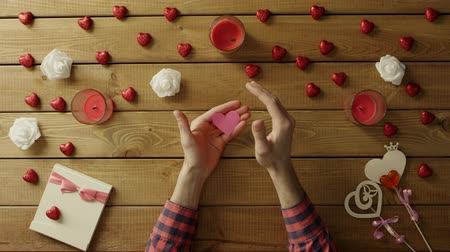 table top shot : Cheerful man with paper heart sits by wooden table, top view Stock Footage