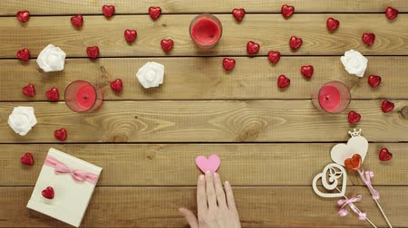 minimalizm : Man in love with paper heart sits by wooden table, top view