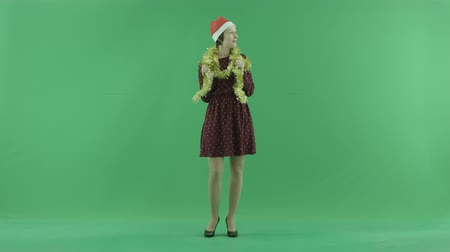 bluntly : A young Christmas woman is looking around on the green screen